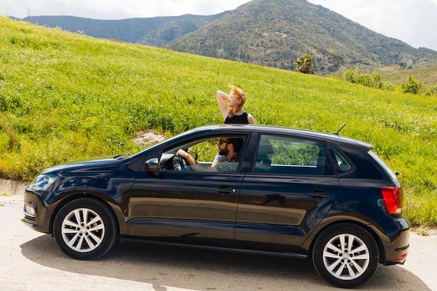 Mulher olhando para a frente saindo da janela do carro Foto gratuita