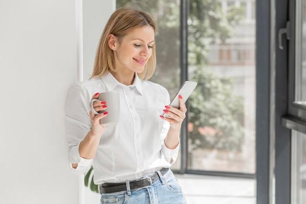 Mulher olhando para o telefone dentro de casa Foto gratuita
