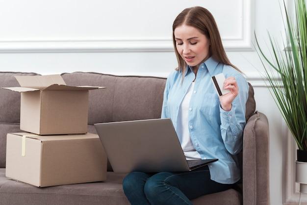 Mulher olhando para seu laptop e segurando o cartão de crédito Foto gratuita