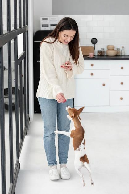 Mulher olhando para smartphone e dando deleites de cachorro Foto gratuita