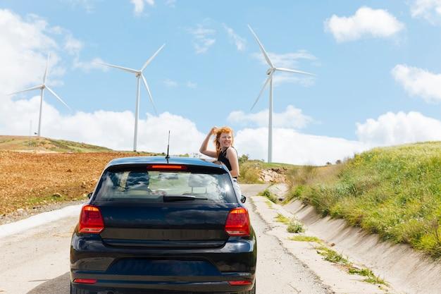 Mulher olhando para trás na estrada fora da janela do carro Foto gratuita