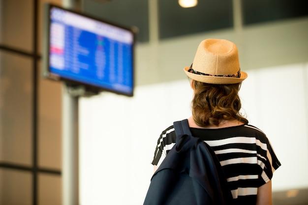 Mulher olhando telas no aeroporto Foto gratuita