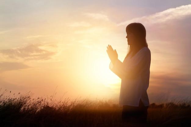 Mulher, orando, e, praticar, meditar, ligado, natureza, pôr do sol, fundo, esperança, conceito Foto Premium