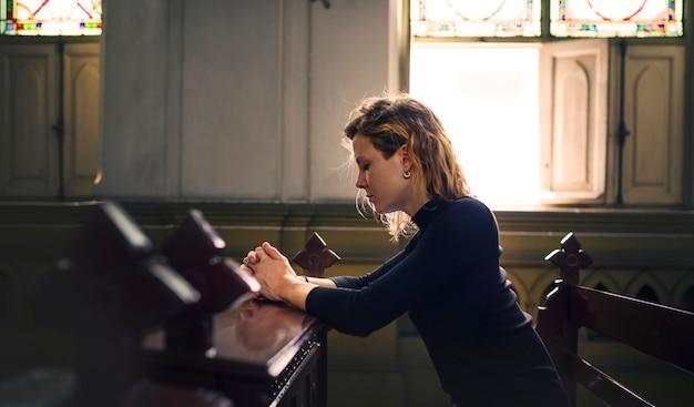 Mulher, orando, em, a, igreja Foto gratuita