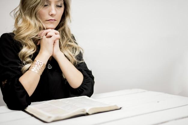 Mulher orando em frente à bíblia em uma mesa sob as luzes Foto gratuita
