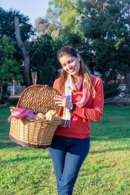 Mulher orgulhosa com a cesta cheia de alimentos saudáveis Foto gratuita