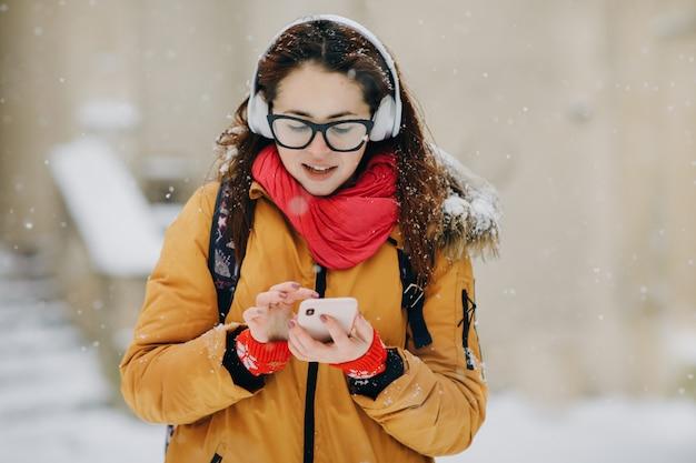 Mulher ouve música no celular na cidade no inverno. retrato close-up jovem na cidade de inverno, sorrindo Foto Premium