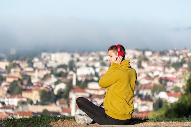 Mulher ouvindo música ao ar livre Foto gratuita