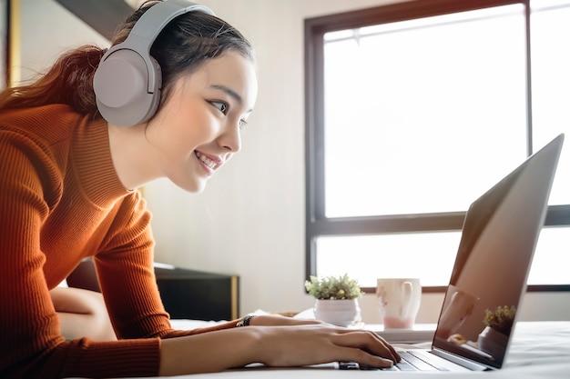 Mulher ouvindo música com fones de ouvido e usando o computador portátil enquanto relaxa em casa Foto Premium