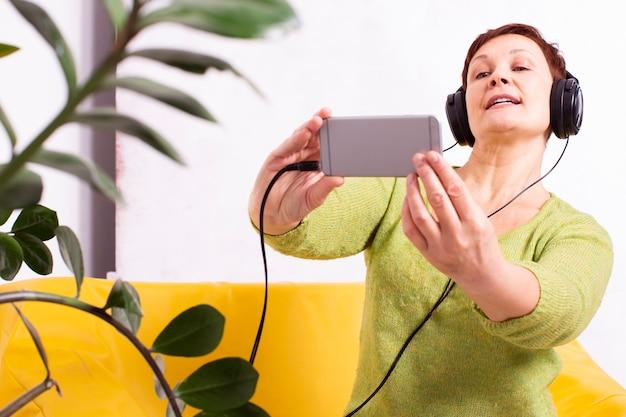 Mulher ouvindo música e tirar uma selfie Foto gratuita