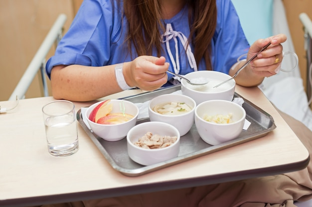 Mulher, paciente, sentar-se cama, em, quarto hospital, comendo alimento Foto Premium
