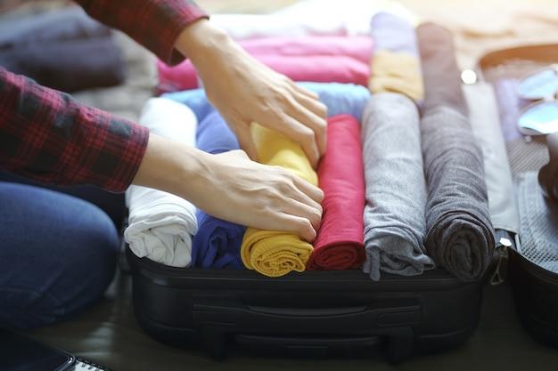 Mulher, pacote mão, roupas, em, mala mala, cama Foto Premium