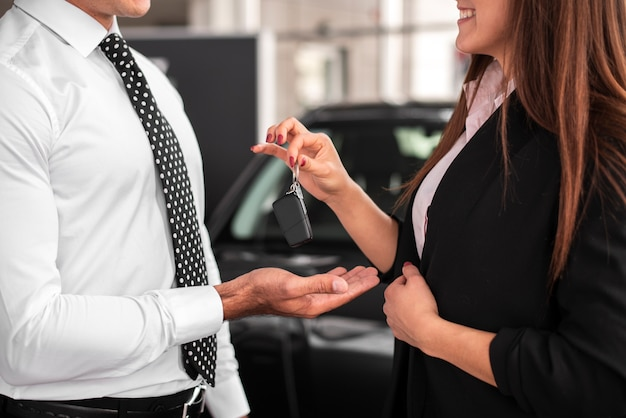 Mulher passando as chaves do carro para um homem Foto gratuita