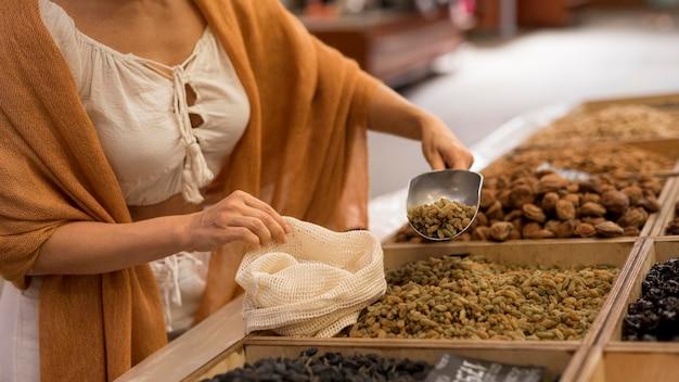 Mulher pegando comida seca no mercado de lado Foto gratuita