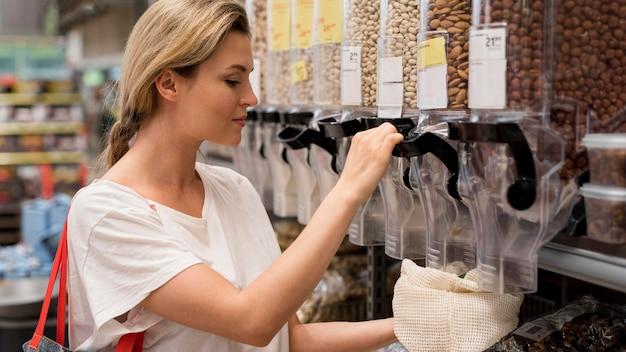 Mulher pegando nozes deliciosas do mercado Foto gratuita