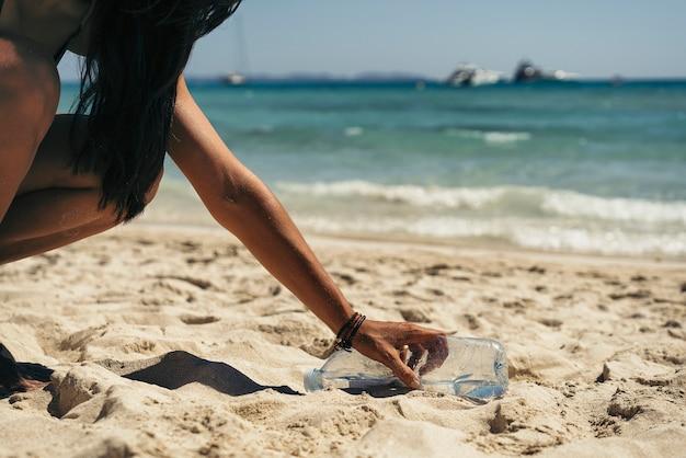 Mulher pegando um lixo de garrafa de água da praia. Foto Premium