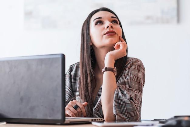 Mulher pensando durante o trabalho no laptop Foto gratuita