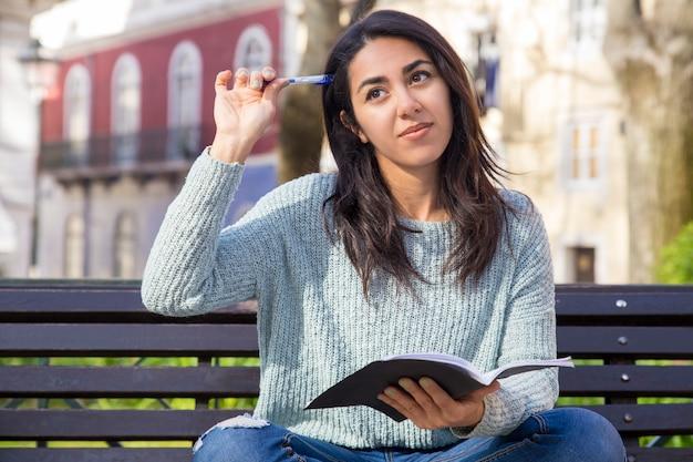 Mulher pensativa, coçando a cabeça com caneta e sentado no banco Foto gratuita