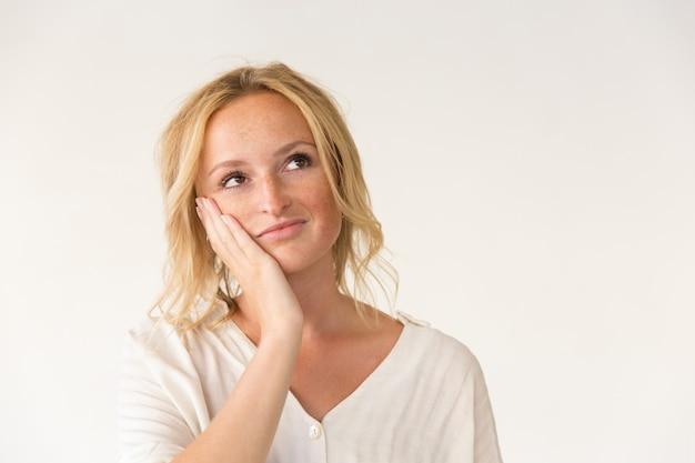 Mulher pensativa com a mão na bochecha Foto gratuita