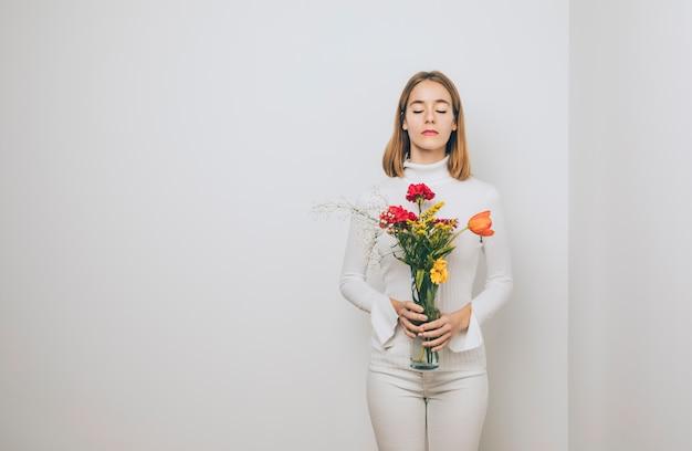 Mulher pensativa com flores brilhantes em vaso Foto gratuita