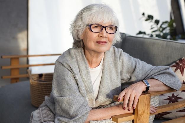 Mulher pensativa, de meia-idade, de cabelos grisalhos, usando óculos, lenço largo e relógio de pulso, passando o tempo de lazer em casa, sentada no confortável sofá da sala de estar, com olhar pensativo Foto gratuita