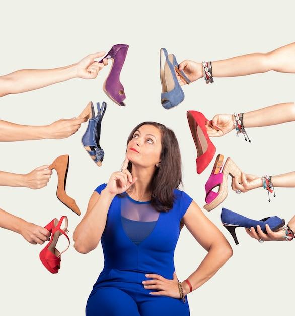 Mulher pensativa, decidindo que sapato ela quer Foto Premium
