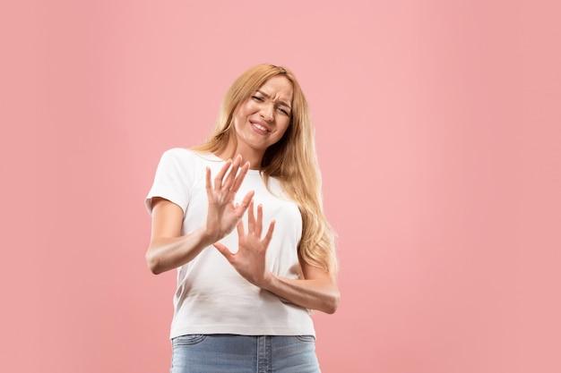Mulher pensativa duvidosa com expressão pensativa fazendo escolha contra parede rosa Foto gratuita