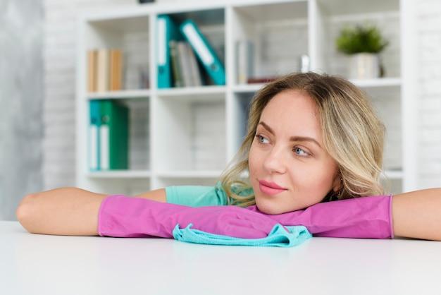 Mulher pensativa, usando luvas de borracha, apoiando-se na mesa branca, olhando para longe Foto gratuita