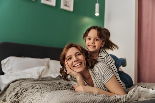 Mulher pequena e a mãe dela estão deitadas na cama, rindo e olhando para a câmera. Foto gratuita