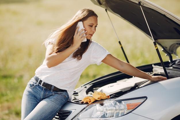 Mulher perto de carro quebrado pedir ajuda Foto gratuita