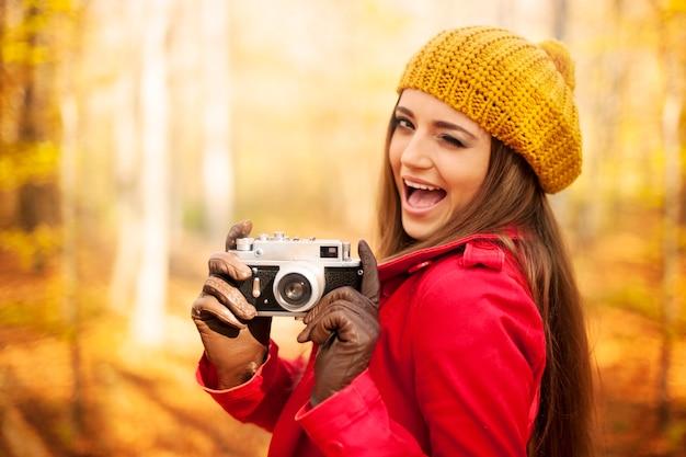 Mulher piscando o olho tirando foto com câmera retro Foto gratuita