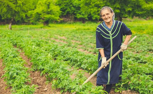 Mulher plantando legumes e sorrindo na fazenda com equipamentos. Foto gratuita