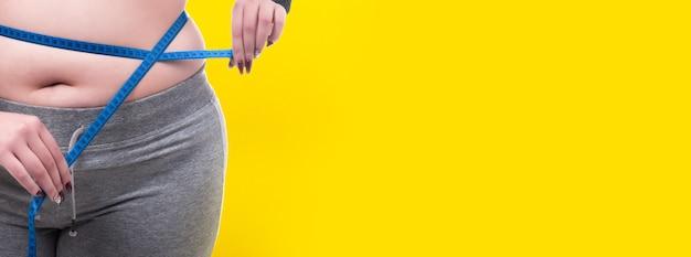 Mulher plus size medindo a cintura na parede amarela, conceito de obesidade Foto Premium
