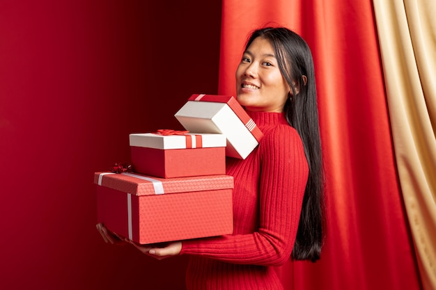 Mulher posando com caixas para o ano novo chinês Foto gratuita