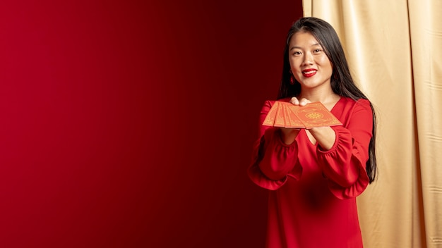 Mulher posando com cartões de ano novo chinês Foto gratuita