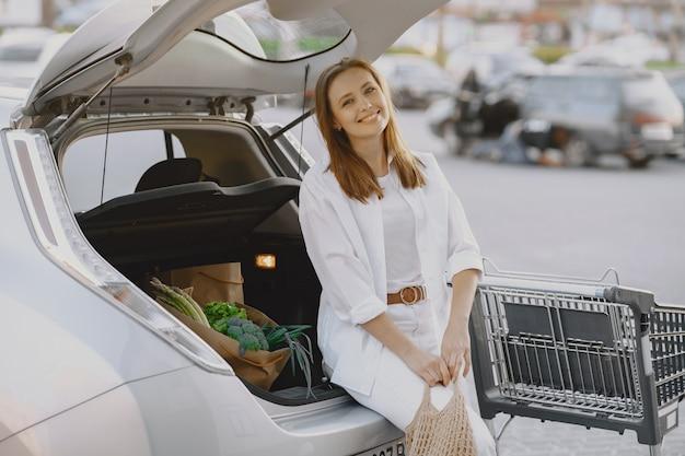 Mulher posando com uma sacola de compras por seu carro Foto gratuita