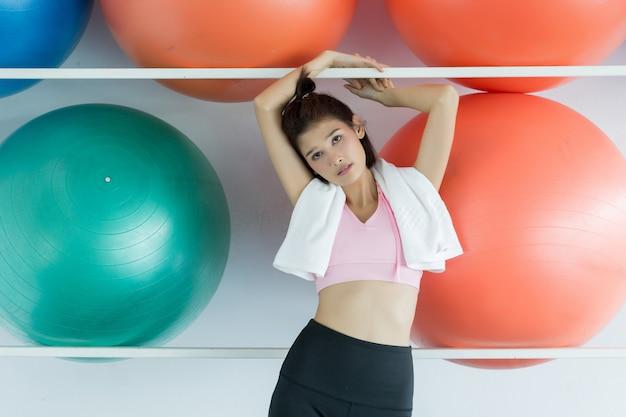 Mulher posando de bola de pilates no ginásio Foto gratuita