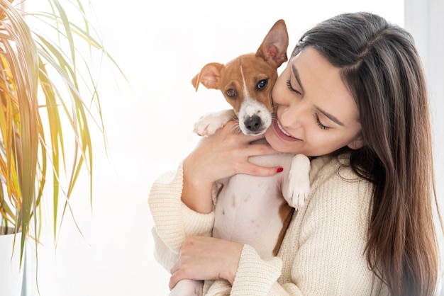 Mulher posando enquanto segura seu cachorro com planta Foto gratuita