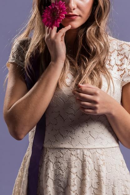 Mulher posando enquanto segura um crisântemo Foto gratuita
