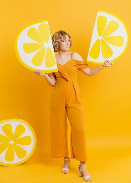 Mulher posando, mantendo decorações de fatias de limão Foto gratuita