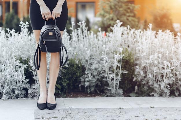 Mulher posando na rua, segurando o saco escuro Foto Premium