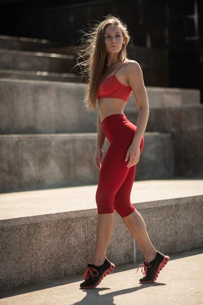Mulher posando perto da fonte da cidade em roupas de ginástica depois de um treino Foto Premium