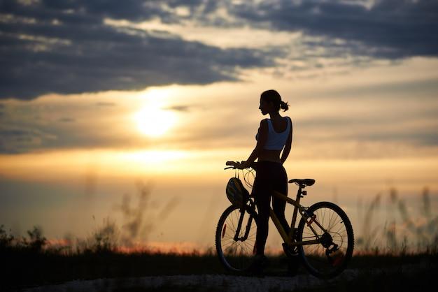 Mulher posando perto de bicicleta e natureza enoying. Foto Premium