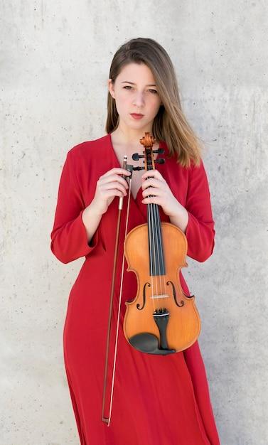 Mulher posando, segurando o violino e arco Foto gratuita