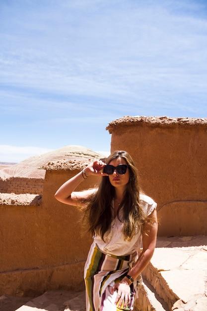 Mulher, posar, em, ruínas deserto, sob, céu azul Foto gratuita