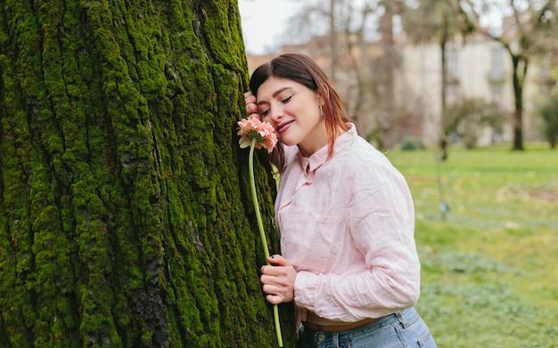Mulher positiva com flor perto de árvore no parque Foto gratuita