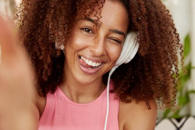 Mulher positiva com penteado espesso e crespo mostra a língua, faz selfie conectada a um dispositivo irreconhecível, ouve músicas favoritas na lista de reprodução com fones de ouvido, aproveita o tempo livre sozinho. etnia, estilo de vida Foto gratuita