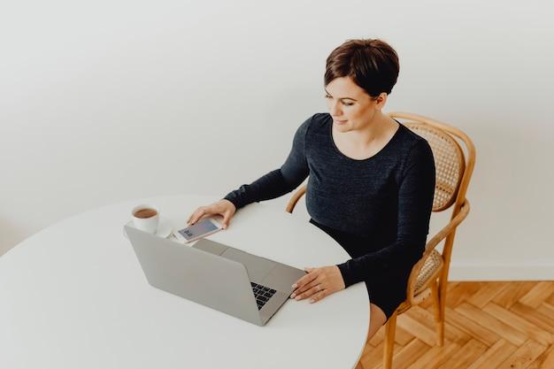 Mulher positiva com uma xícara de chá teletrabalho Foto gratuita