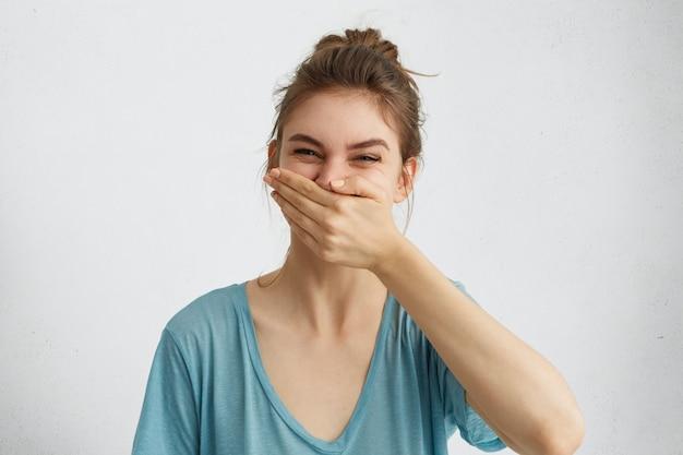 Mulher positiva rindo enquanto tem bom humor durante o tempo livre, tentando controlar suas emoções, cobrindo a boca com a mão. Foto gratuita