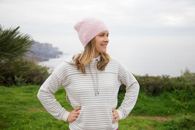 Mulher positiva, vestindo roupas esportivas e relaxante ao ar livre Foto gratuita
